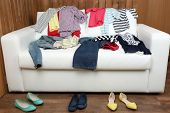 Colorful clothing on white sofa and female shoes on wooden planks background