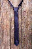 Trendy tie on wooden planks background