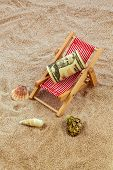 beach chair with dollars on the sandy beach. symbolic photo for cost of travel, vacation, holidays. save on vacation