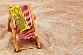 a deck chair with a euro banknote. photo icon for save on holiday and when traveling