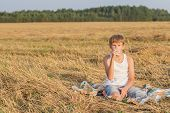 Teenage Boy In Farm Field Having Break