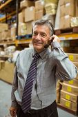 Smiling manager talking in a headset in a large warehouse