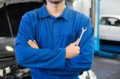 Mechanic standing with arms crossed at the repair garage
