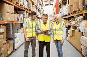 foto of clipboard  - Manager writing on clipboard talking to colleague in a large warehouse - JPG