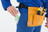 Cropped image of repairman putting euro notes in pocket against white background
