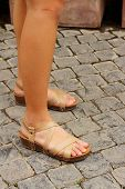 Woman Wearing Brown Shoes Standing On A Cement Floor.