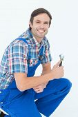 Portrait of confident plumber holding adjustable wrench over white background