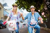 Hip young couple going for a bike ride against valentines heart design