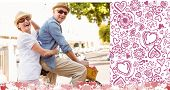 Happy mature couple going for a bike ride in the city against valentines pattern