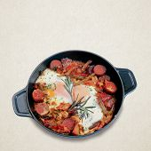 Fried Eggs With Sausages In A Black Pan