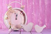 Beautiful vintage clock with decorative birds on table on wooden background