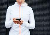 Woman In Sportswear Using Mobile Phone