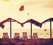 Vintage Filtered Picture Of Beach And Paragliders At Sunset.