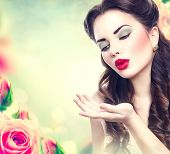 Retro woman portrait in beauty pink roses garden. Beautiful Vintage styled girl with flowers. Perfect makeup and hairstyle. Gorgeous model lady. Red Lips. Luxury Make up and Hair. Vogue Style