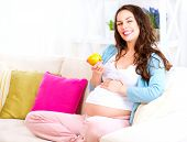 Pregnant Happy Woman sitting on a sofa and eating apple. Mom Expecting Baby. Healthy eating, diet, dieting. Pregnant Woman Belly. Pregnancy. Baby Shower