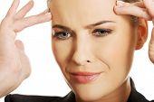 Beautiful businesswoman having huge headache