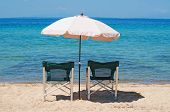 Two chairs and umbrella on the beach with sea horizon in the background