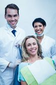 Portrait of happy male dentist with assistant and female patient