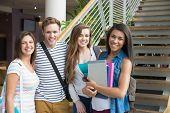 Smiling students looking at camera outside at the university