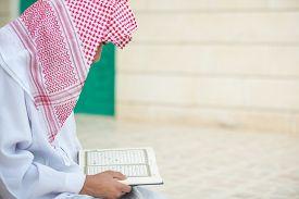 pic of muslim man  - Young Arabic Muslim man reading Koran and praying - JPG