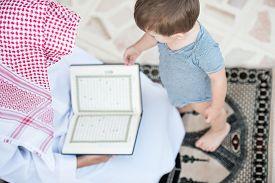 stock photo of muslim man  - Young Arabic Muslim man reading Koran and praying - JPG
