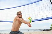picture of passed out  - Beach volleyball man playing game hitting forearm pass volley ball during match on summer beach - JPG