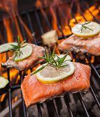 stock photo of salmon steak  - Delicious grilled salmon steaks on fire - JPG