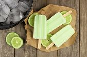 picture of lime  - Homemade lime yogurt popsicles with fresh lime slices on paper with rustic wood background - JPG