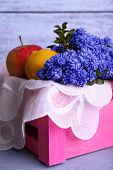 pic of blue-bell  - Blue bell flowers with fruits in crate on wooden background - JPG