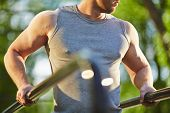 pic of vest  - Active man in grey vest doing exercise for arms outdoor - JPG