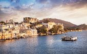 pic of palace  - Lake Pichola with City Palace view at cloudy sunset sky in Udaipur Rajasthan India - JPG