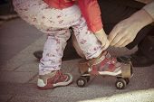 stock photo of roller-skating  - Father helping her little daughter to try on vintage roller skates - JPG