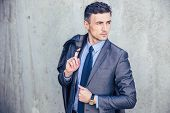 image of thoughtfulness  - Portrait of a thoughtful businessman holding jacket on shoulder and looking away - JPG