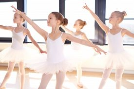 picture of ballerina  - Choreographed dance by a group of graceful pretty young ballerinas practicing during class at a classical ballet school - JPG