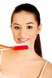 foto of enormous  - Woman brushing her teeth with enormous brush - JPG