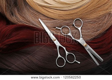 Hairdresser\'s scissors with varicolored strands of hair, close up