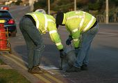 Workmen line-painting road signs