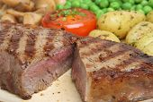 Rare sirloin steak with new potatoes, peas and mushrooms.