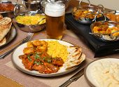 Indian chicken jalfrezi with potato curry, naan and rice. Shallow DoF, focus on the jalfrezi.
