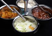 Indian pickles including lime, brinjal, mint raita and onion salad.