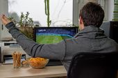 Постер, плакат: Male Gamer Playing Football Game On Computer With Snacks Lying On Table