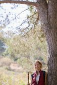 African American female hiker leaning on tree