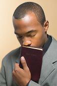 Man with eyes closed kissing Bible