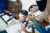 stock photo of pep talk  - Low angle view of coach with basketball players in huddle - JPG