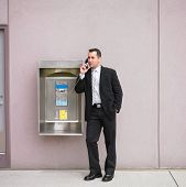 Businessman talking on payphone