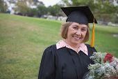 Older graduate holding flower bouquet