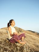 Senior woman meditating on a rock outdoors