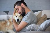 hipster man snuggling and hugging his dog, close friendship loving bond between owner and pet husky poster