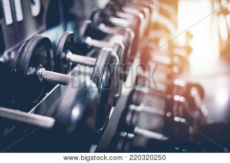 poster of Black Steel Dumbbell Set. Close Up Of Dumbbells On Rack In Sport Fitness Center. Workout Training An