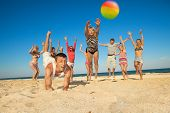 stock photo of beach party  - Group of young joyful people playing volleyball on the beach - JPG